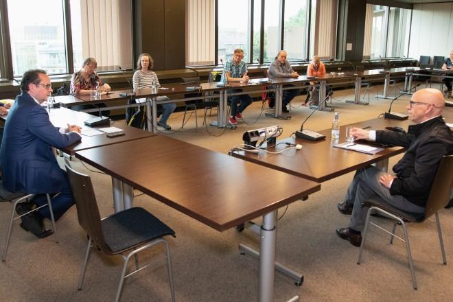 Foto: Mehrere Personen sitzen an einer großen Besprechungsrunde zusammen.