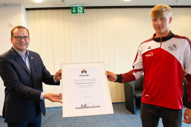 Oberbürgermeister Thomas Kufen überreicht die Glückwunsch-Urkunde der Stadt Essen.