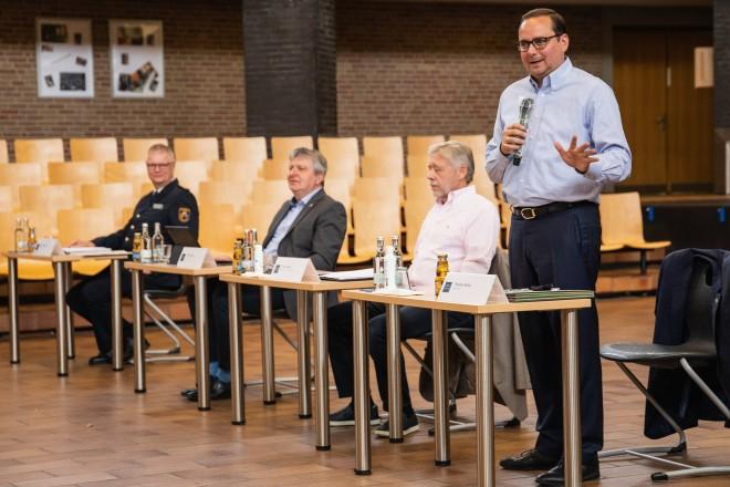 Foto: Vier Personen sind an jeweils einem Tisch platziert. Eine von Ihnen steht uns spricht in ein Mikrofon.