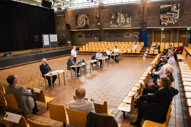 Foto: In der Mitte eines großen Saals sind sechspersonen an jeweils einem Tisch nebeneinander aufgereiht. Eine der Personen steht mit einem Mikrofon in der Hand. Mehrere Menschen sitzen um sie herum.