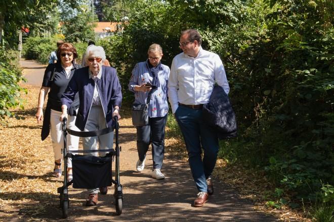 Foto: Vier Personen laufen an einem grün bewachsenen Weg. Eine peron geht an einem Rollator.