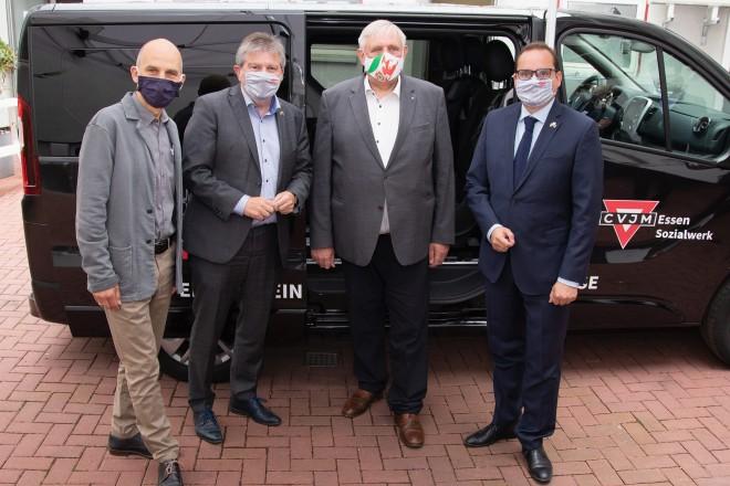 """Foto: Vier Personen mit Mund-Nase-Schutzmasken stehen vor einem Lastenwagen, mit der Aufschrift """"CVJM Essen Sozialwerk""""."""