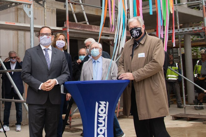 Foto: Mehrere Personen stehen an einer Baustelle.