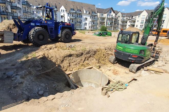 Foto: Baustelle mit mehreren Baustellenfahrzeugen, eine Öffnung im Erdreich