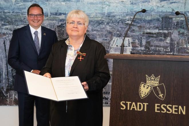 Oberbürgermeister Thomas Kufen übergibt Karla Brennecke-Roos das Verdienstkreuz am Bande.