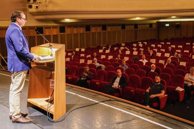 Foto: Eine Person steht an einem Rednerpult und spricht zu einem Publikum.
