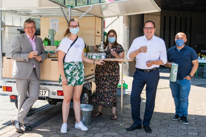 Foto: fünf Personen steheh an einer mobilen Teeküche und trinken Tee.