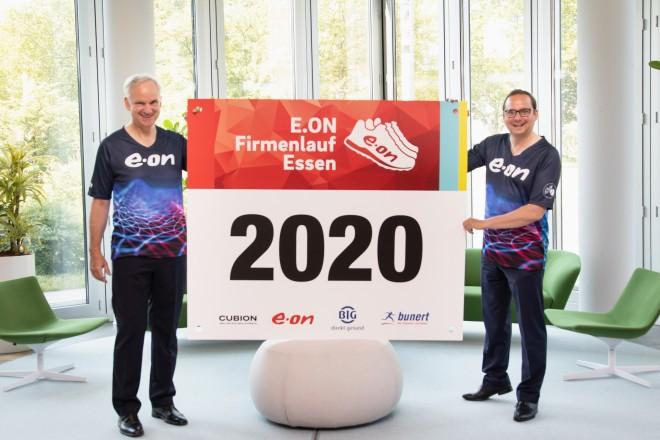 """Foto. zwei personen halten ein Schild, auf dem steht """"E.ON Firmenlauf Essen 2020""""."""
