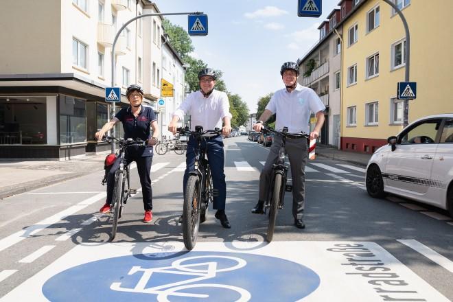 Foto: drei Personen sitzen auf Fahrrädern.
