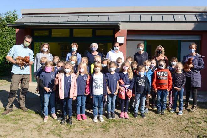 Oberbürgermeister Thomas Kufen bei der Übergabe der Schulhühner an die Grundschule Gerschede.