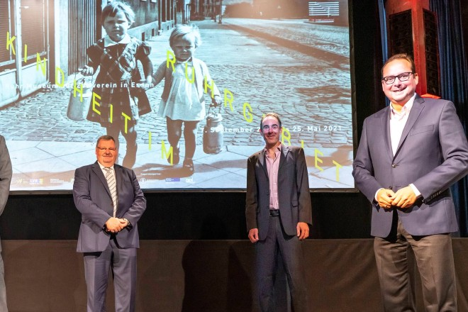 Foto: Vier Personen stehen vor einer Projektionswand
