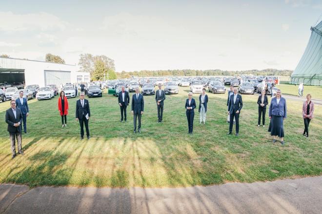 Foto: Mehrere Menschen stehen auf einer Wiese für ein Gruppenfoto beisammen.