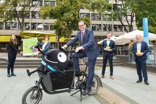 Foto: Fünf Personen stehen für ein Gruppenfoto beieinander. Zwei halten ein Plakat in die Kamera. Eine sitzt auf einem Fahrrad. Zwei halten Broschüren in der Hand.