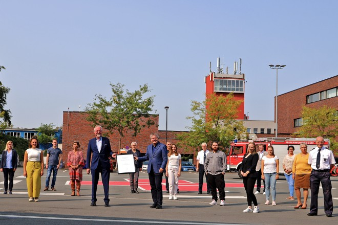 Foto: Prof. Dr. Budde überreicht Gesundheitsdezernent Peter Renzel (Mitte) in Anwesenheit von Mitarbeiter*innen des LZUGB die Auszeichnung auf dem Gelände der Essener Feuerwehr.