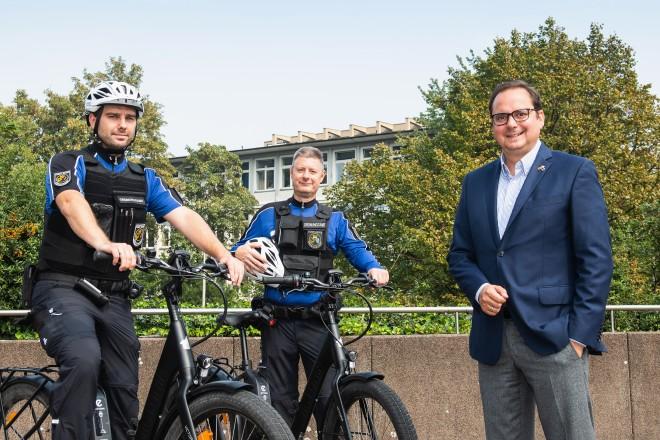 Foto: Zwei Mitarbeiter der neuen Essener Fahrradstreife des kommunalen Ordnungsdienstes mit Oberbürgermeister Thomas Kufen.