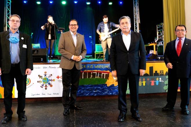 Foto: Vier Personen stehen vor einer Bühne. Hinter Ihnen stehen auf der Bühne zwei Personen. Die rechte hält ein Mikrofon in der Hand, die andere spielt an einer E-Gitarre.