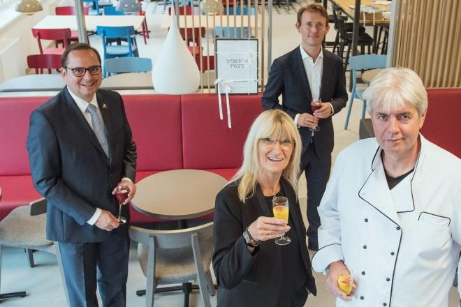 Foto: vier Personen. Jede hält ein Glas in der Hand.