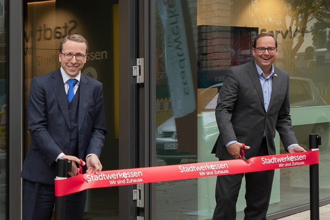 """Foto: Zwei Personen stehen vor einem Hauseingang, mit der Überschrift """"Kundenzentrum Stadtwerkessen"""". Die beiden Personen schneiden ein rotes Band durch."""