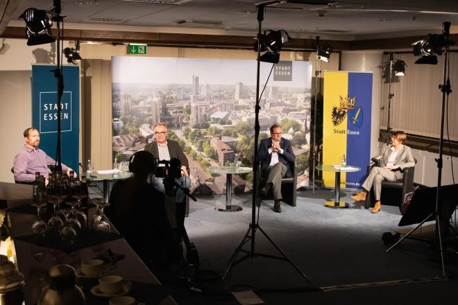 Foto: in einem Fernsehstudio sitzen vier Personen auf vier sesseln verteilt.