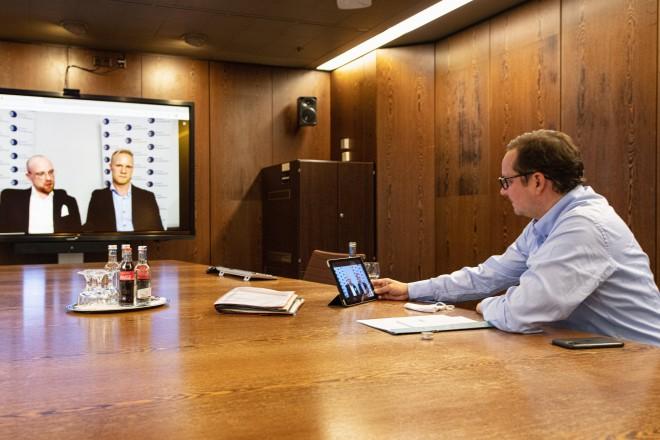 Foto: Eine Person Sitzt am Tisch und schaut auf einen Monitor.