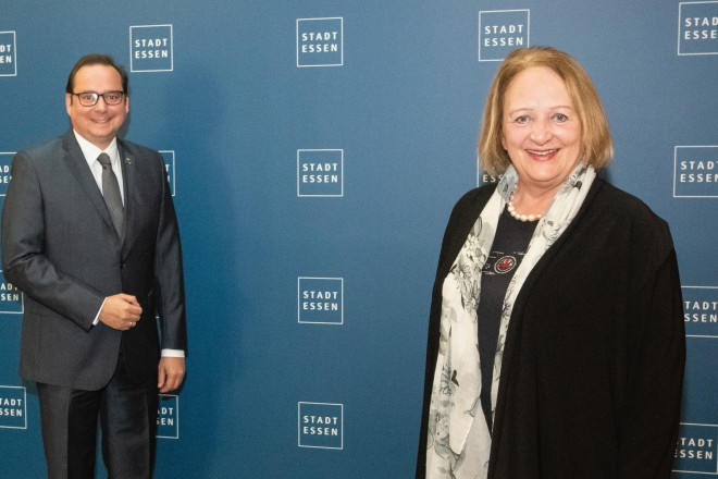 Foto: zwei Personen vor blauer Wand