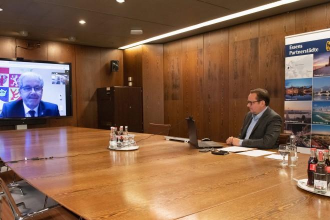 Foto: Eine Person sitz an einem Tisch mit einem Klapprechner. Imhintergrund ist eine andere Person auf einem Bildschirm zu sehen.