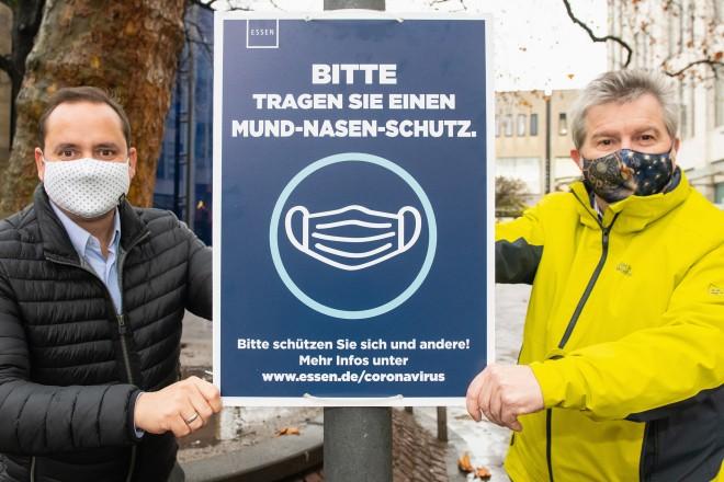 Oberbürgermeister Thomas Kufen und Stadtdirektor Peter Renzel mit der neuen Beschilderung, die das Tragen eines Mund-Nasen-Schutzes empfiehlt.
