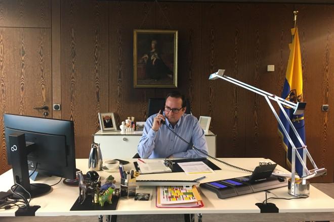 Foto: Oberbürgermeister Thomas kufen telefoniert an seinem Schreibtisch mit der Kassenärztlichen Vereinigung