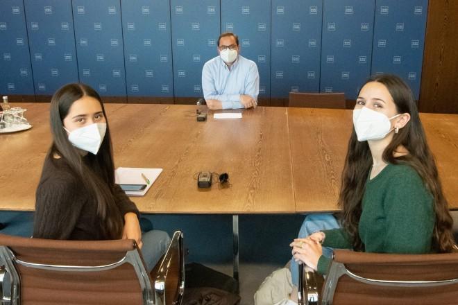 Foto: Gruppenfoto. Fünf Personen sitzen an einem Tisch