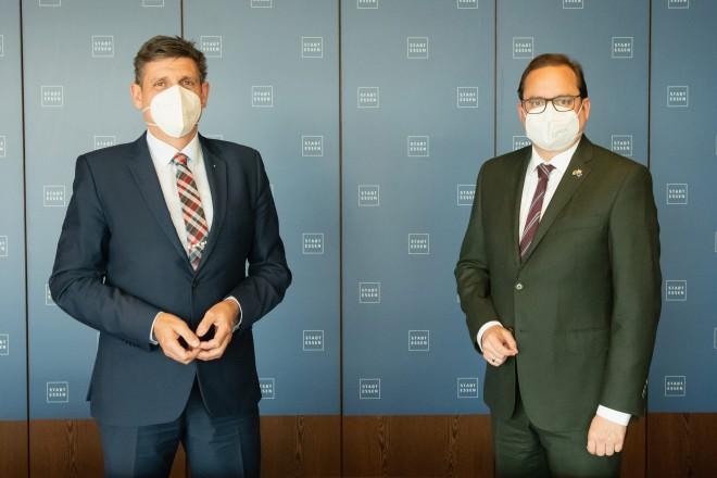 Foto: Zwei Personen stehen vor einer blauen Wand.