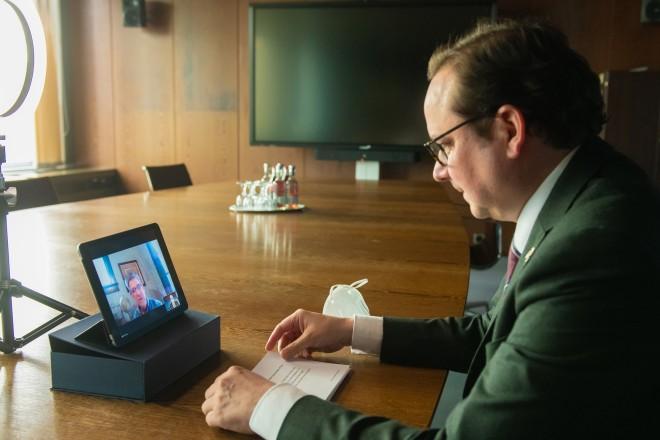 Foto: Eine Person sitzt in einer Videokonferenz mit Tablet-Rechner.