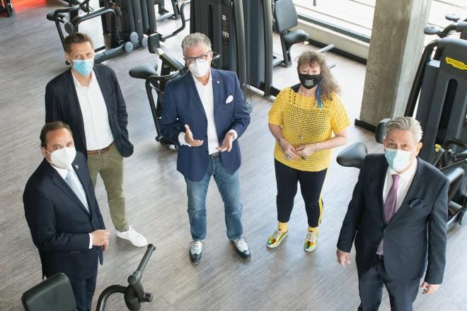 Foto: fünf Personen stehen in einem Raum voller Sportgeräten
