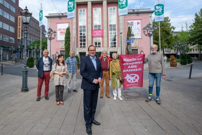 Stadt Essen zeigt Flagge gegen Atomwaffen: Oberbürgermeister Thomas Kufen (Mitte) mit Mitgliedern des Essener Friedensforums.