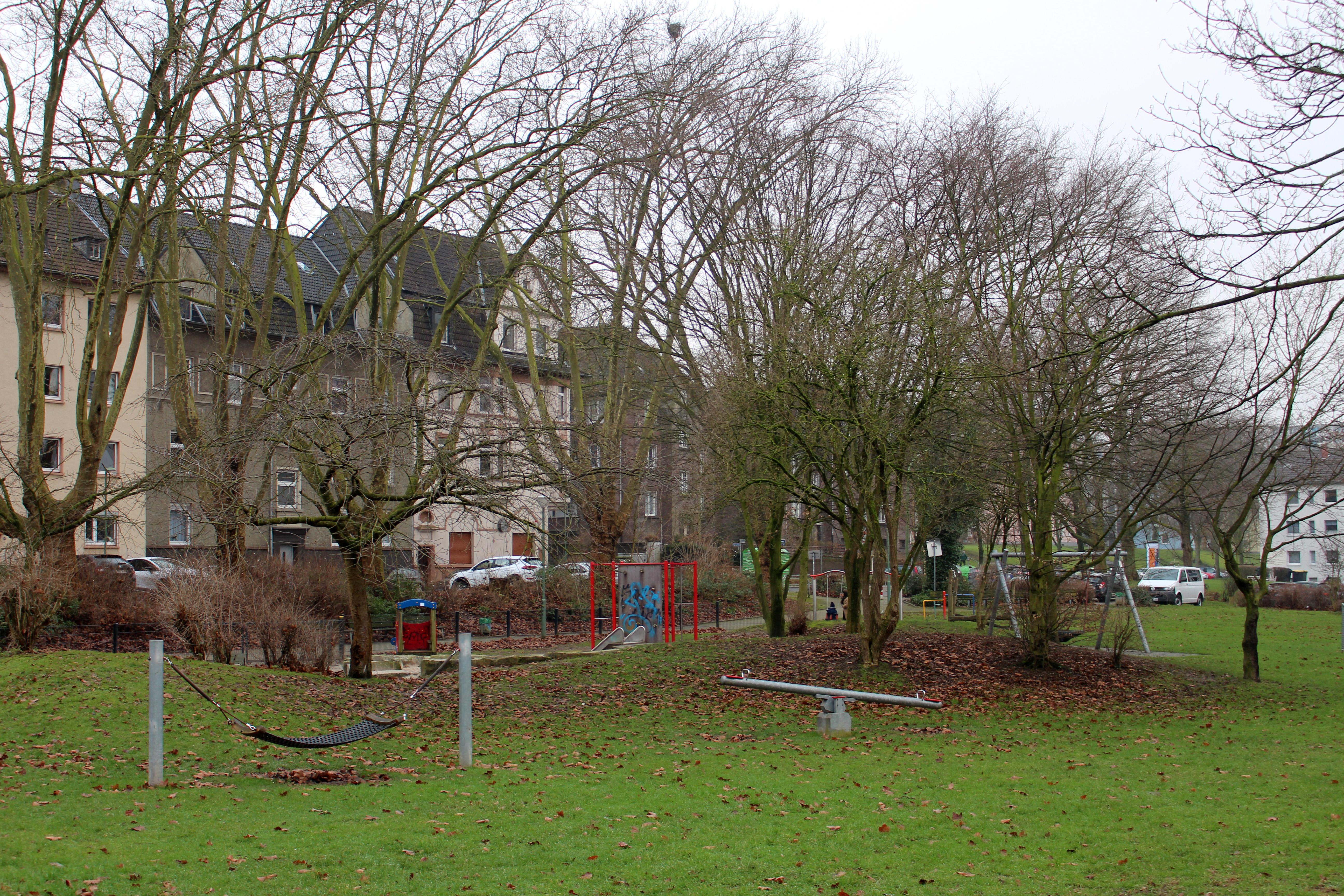 Spielplatz auf einer grünen Wiese, der sich vor einer Häuserreihe und blattlosen Bäumen befindet