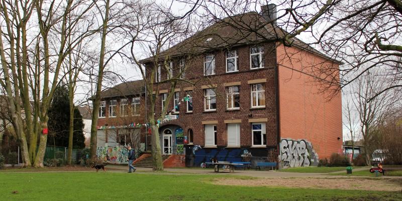 Altes, braunes Haus hinter einem kleinen Spielplatz