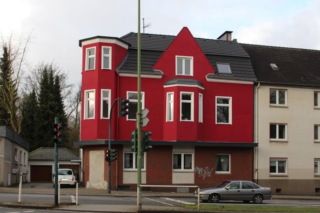 Rotes Eckhaus hinter einer Straße mit einer Ampel