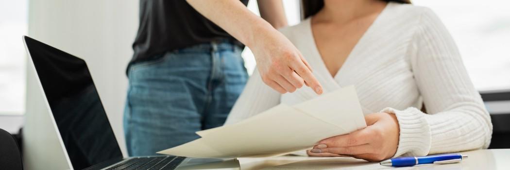 Eine Person berät eine andere indem sie auf einen Zettel zeigt.